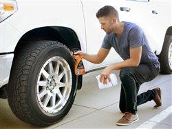 man using wheel cleaner on tire