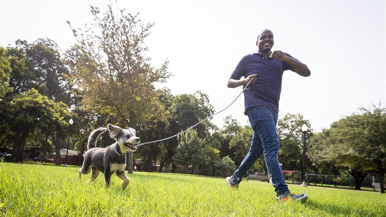 man walking his dog in the grass