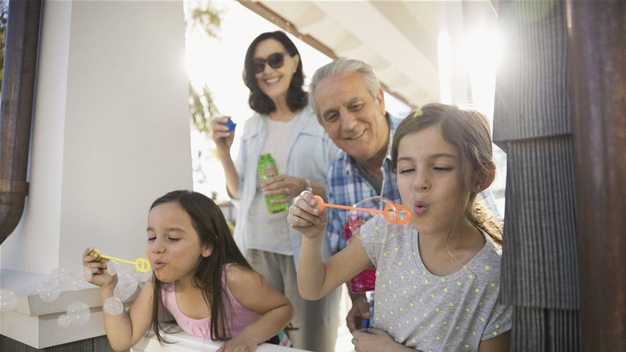 extended family enjoying blowing bubbles on the front porch