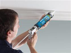 man using caulking along crown molding