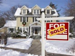 lovely two-story house with snow all around and sold sign in the front yard