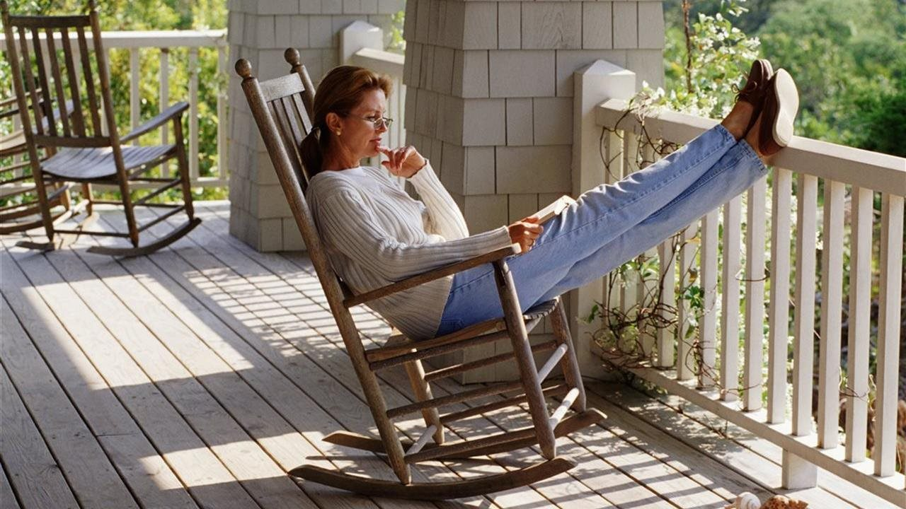woman enjoying a book on the deck