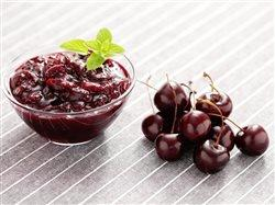 Cherry preserves in a bowl with cherries next to it that can give your holidays a healthy twist