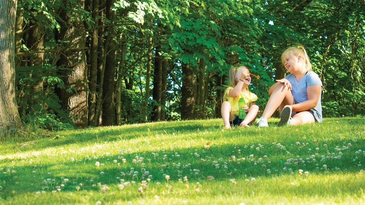two little girl sitting on the grass in the backyard