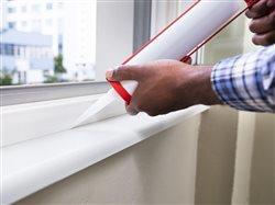man caulking a window sill