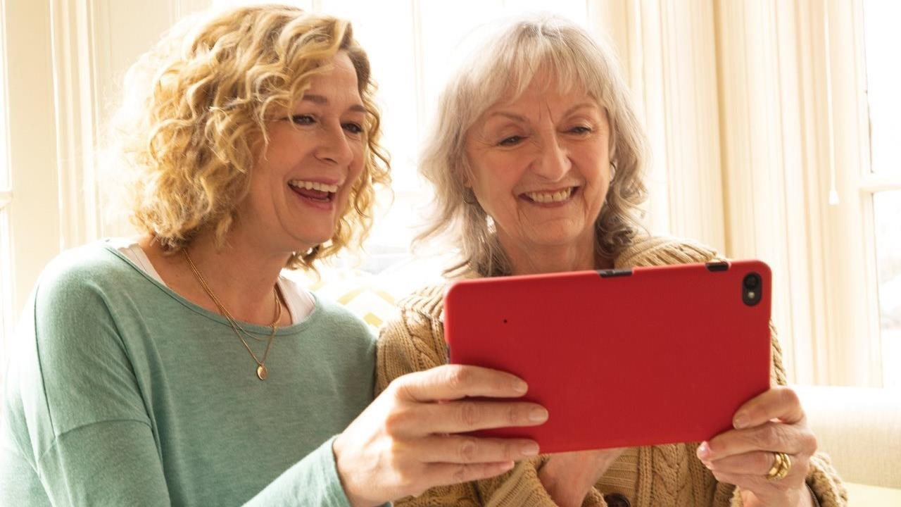 2 mature women looking at a tablet