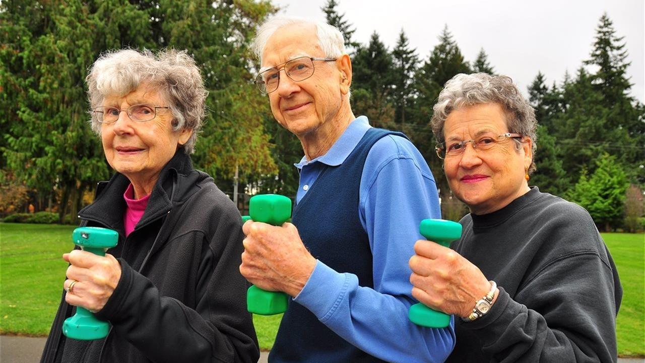 Three older people using hand weights