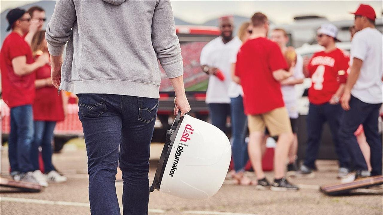 man walking with dish for TV at tailgating party