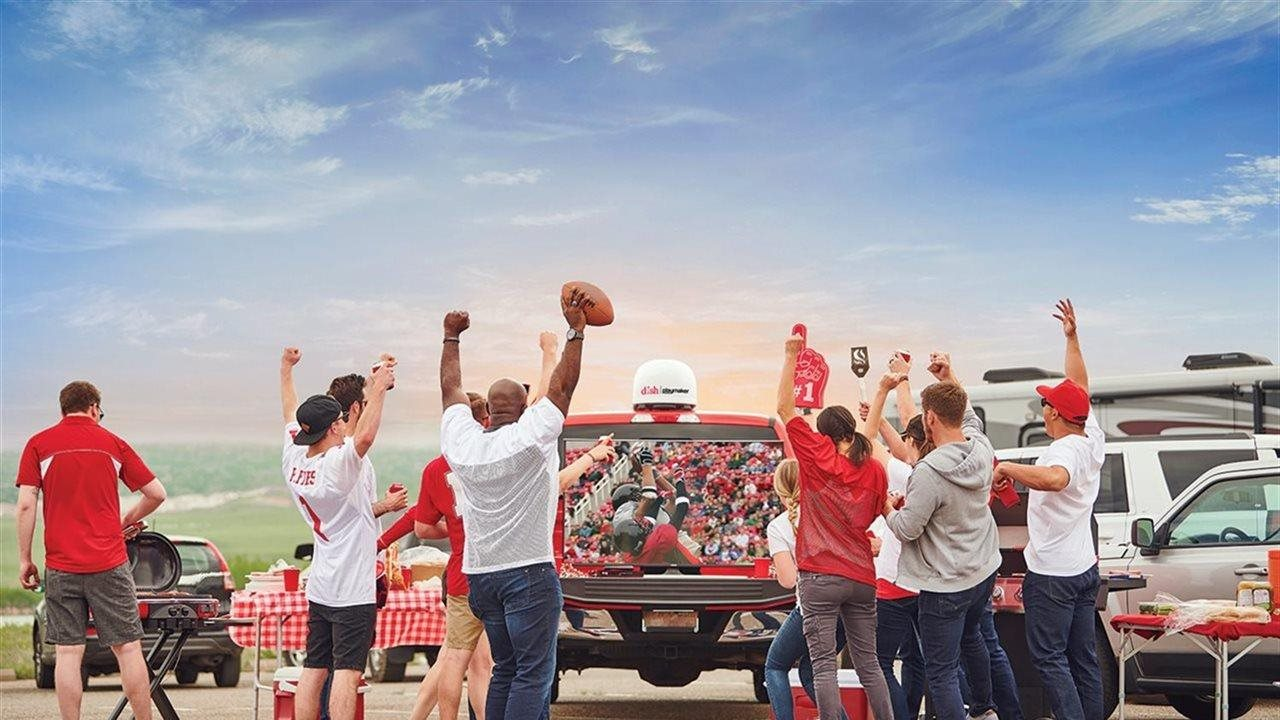 group of people tailgating with a giant TV and dish