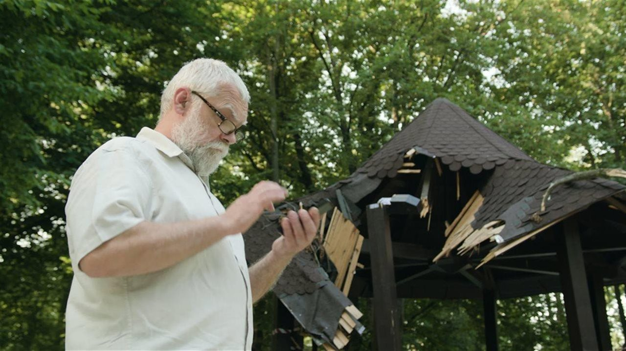 man with storm damage using cell phone