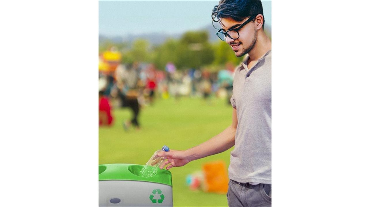 man placing a plastic water bottle in a recycling bin.