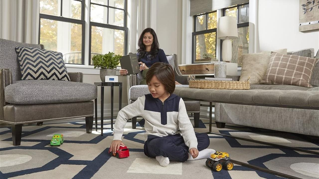 mom smiling seated in chair and son playing with toys on the floor of the lioving room