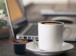 hot coffee on a cup by a laptop on a desk with a pod next to the cup