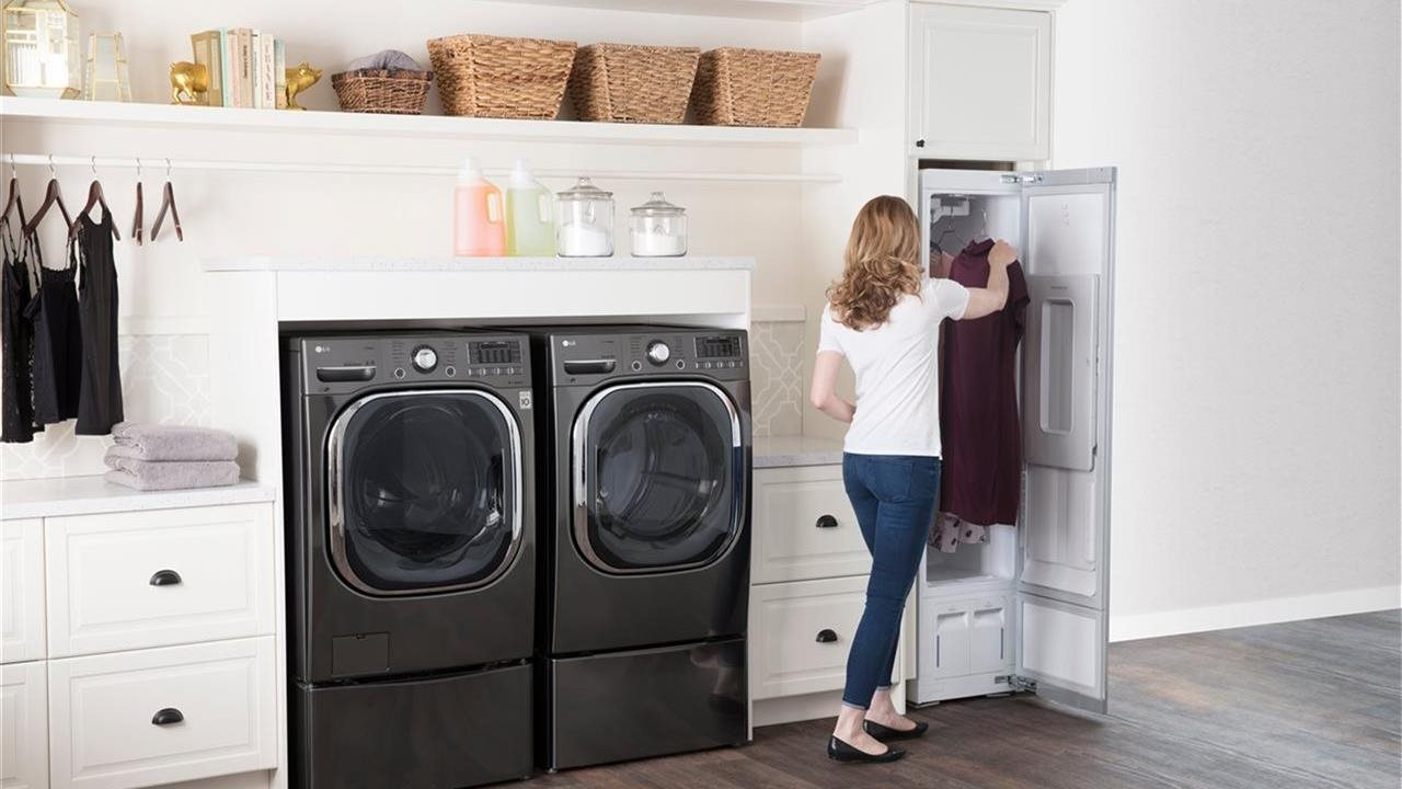 woman using LG clothes Styler in her laundry room